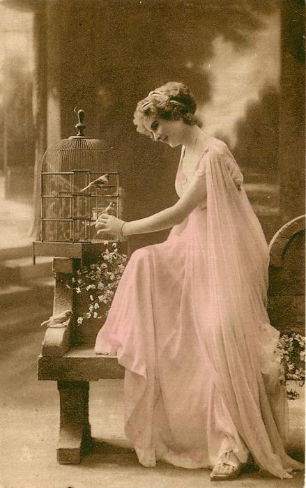 girl with bird in cage looks down at another perched on seat