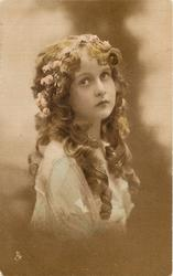 girl with flowers in hair, long curls in front, faces right, looks up