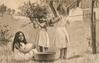 three girls play outside in country, girl on left seated on grass, other two hang washing on line
