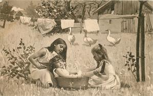three girls play outside in country, two larger girls pretend to bath smallest, washing line & geese behind