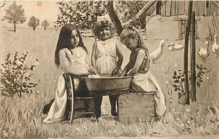 three girls play outside in country, washing clothes in bowl