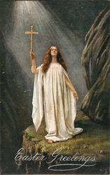 woman holding crucifix in hand on cliff ledge, light from above