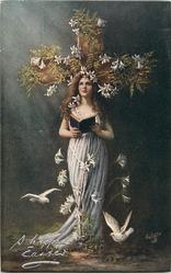 woman stands in front of cross holding open book, looking up, two doves below