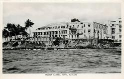 mid-distant  view of  hotel from sea , palms left