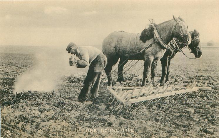 UNE BONNE PIPE  farmer lights pipe from fire in field, horses & harrow right