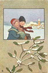 inset of day winter scene, boy & girl in snow, village behind right, snow on mistletoe below