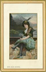 MISS JEAN AYLWIN  Scottish attire, heather in both hands, sitting on rocks, legs crossed