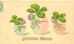 three easter eggs each with clover tied to them with gilt ribbon