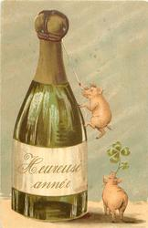 HEUREUSE ANNEE (on bottle)  small pig uses rope to climb enormous chapagne bottle, another with 4 leaf clover in mouth stands below