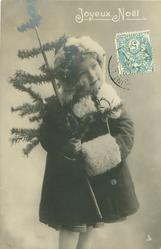 young girl dressed for winter with fur cap, cape & muff, stands facing front, looking up & right, tree held with both hands