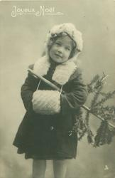 young girl dressed for winter with fur cap, cape & muff, stands facing front , tree under her left arm