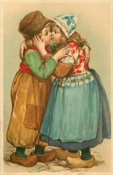 boy in brown trousers stands left kissing Dutch girl in blue skirt right