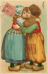 boy in brown trousers stands right, kissing Dutch girl in blue skirt left