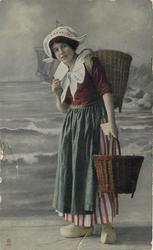 Dutch girl holds letter to her chin, basket on  back & carries another in left hand, bl/w  background of coast & sailing ship