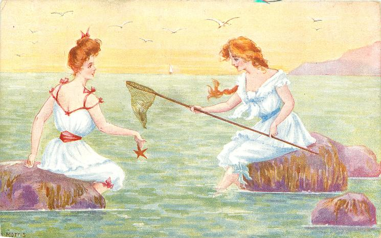 2 girls in old-style bathing dresses sit on rocks in sea, girl left dangles a starfish, girl right holds a net