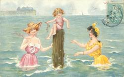 2 girls in old style bathing dresses in sea on either sde of small girl sitting on top of a post