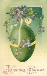 green Easter egg suspended on yellow/white ribbons, violets above