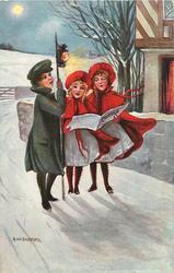 three girls sing carols in the snow