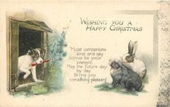 WISHING YOU A HAPPY CHRISTMAS verse, two rabbits look at dog holding carrot in his mouth
