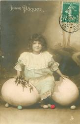 girl kneels holding catkins between fantasy eggs, Easter eggs on ground