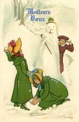 two girls making snowballs to throw at  boy hiding behind snowman
