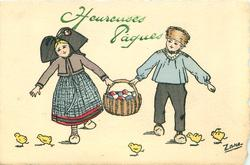 boy right, girl left, carrying basket of Easter eggs between them, five chicks around