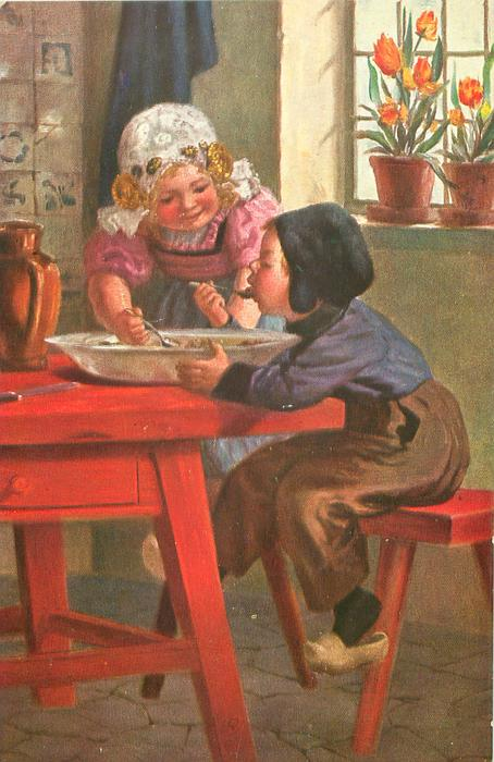 boy right & girl back eat from large bowl on red kitchen table
