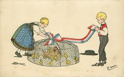 girl left bends to adjust ribbon on top of cage containing hen & chicks, boy holds other end of ribbon, right