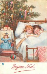 CHRISTMAS MORNING  two children in bed beside toys & tree
