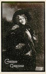 CHRISTMAS GREETINGS  pretty girl in fur coat in snow storm, standing, looking front