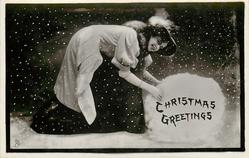 CHRISTMAS GREETINGS  pretty girl makes enormous snowball, snow falls