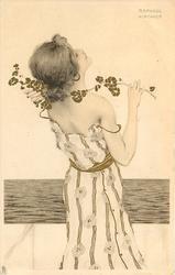 girl looks up and out to sea, spray of flowers over her right shoulder