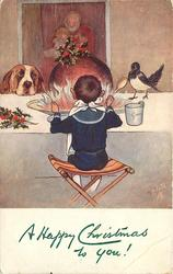 boy on stool sitting in front of large Christmas pudding flambe, dog & magpie observe