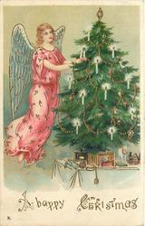 A HAPPY CHRISTMAS  angel  in pink to left of Christmas tree
