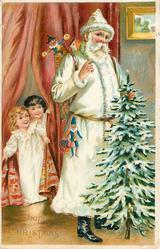 A HAPPY  CHRISTMAS  white robed Santa holds snowy Christmas tree, two children peek through curtain
