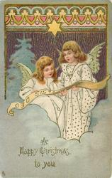 A HAPPY CHRISTMAS TO YOU, two angels in white sing from a scroll, ornate design above