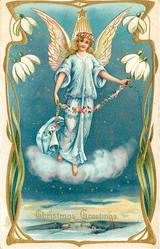 CHRISTMAS GREETINGS  angel  in blue stands on clouds, ornate border with snowdrops