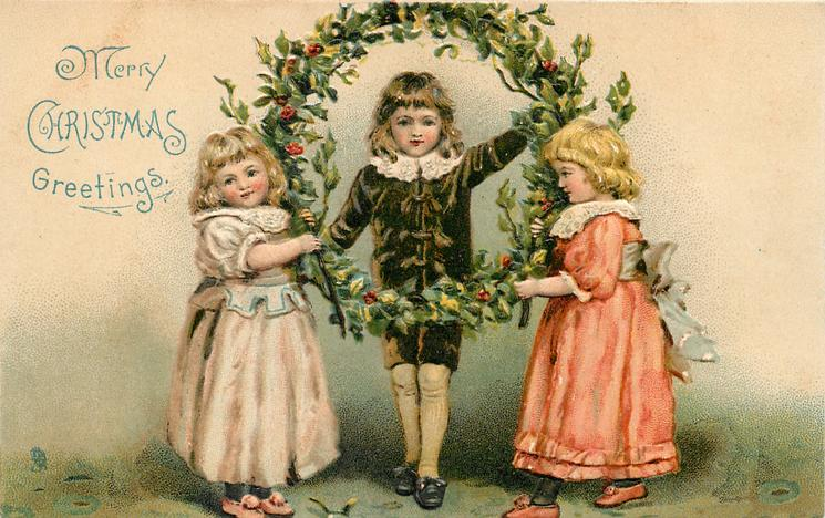 MERRY CHRISTMAS GREETINGS  boy in black suit stands in holly wreath held up by two girls