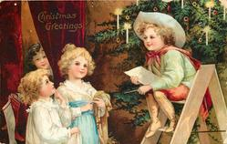 CHRISTMAS GREETINGS  two girls left front, another peeks from between curtains, tree behind boy sitting on step ladder right