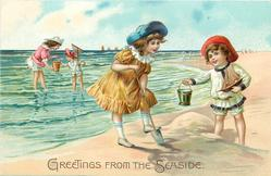 two girls on beach to right, right one holds out pail, left one digs, two others behind in water