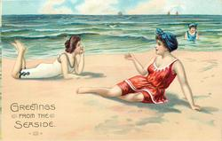 two women on beach, one on left has legs in air, one on right leans on left arm, woman in sea behind