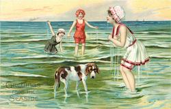 woman in red trimmed white suit stands shivering in sea, dog at her feet, 2 women in water behind