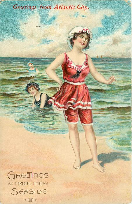 woman on beach in red suit and white hat, two in sea behind