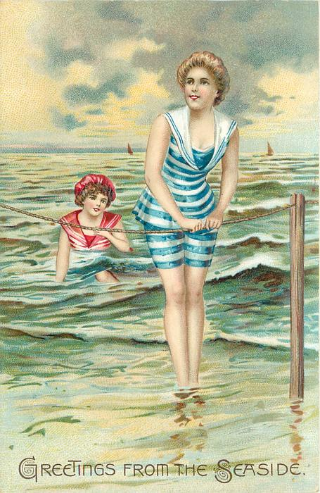 woman on beach in striped blue/white bathing-suit holds rope with both hands, another in sea behind
