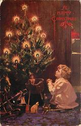 child in long night dress sits on floor by lighted Christmas tree
