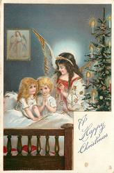 A HAPPY CHRISTMAS  angel over two small children, one praying, in bed