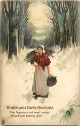 TO WISH YOU A HAPPY CHRISTMAS  young woman walks front in snow carrying wood & basket