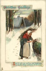 CHRISTMAS GREETINGS  woman carying wood bends right, lighted cottage behind
