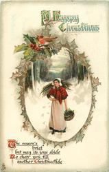 A HAPPY CHRISTMAS  young woman walks front in snow carrying wood & basket