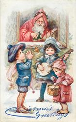 Santa leans out of window watching three children play music